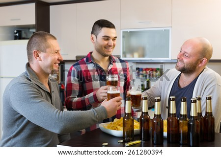 Three happy male friends with glasses of beer and chips indoor