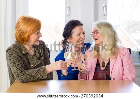 Three Happy Mom Friends Enjoying Glasses of Champagne at the Table Inside a Restaurant While Talking Funny Stories of their Lives. - stock photo