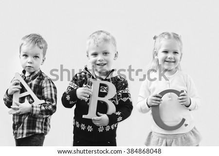 three happy pre-school toddlers with abc letters   - stock photo