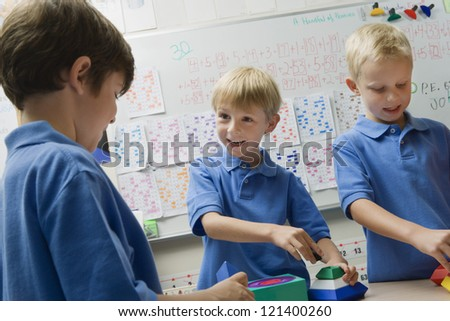 Three happy preadolescent boys solving puzzle game in a playschool - stock photo