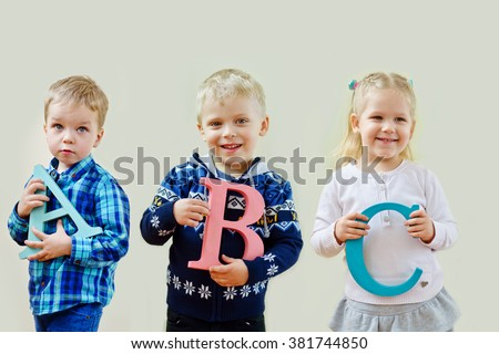 three happy prescholler toddlers with a b c letters