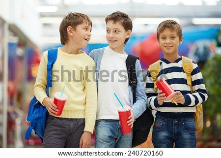 Three happy schoolboys with backpacks - stock photo