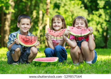 Three happy smiling   child eating watermelon in park - stock photo