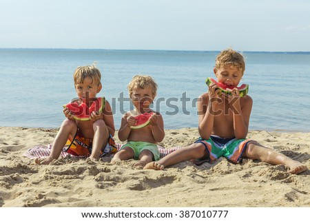 Three happy smiling child eating watermelon on the beach.