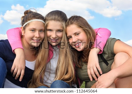 Three happy smiling girls hug at background of sky with clouds. - stock photo