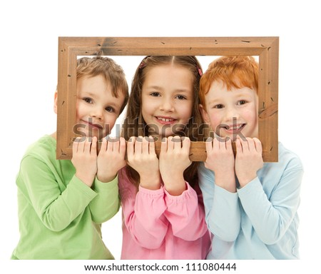 Three happy smiling kids looking through picture frame. Isolated on white.