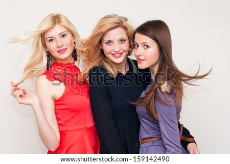 Three happy smiling & looking at camera beautiful fashion women with flying hair studio shot - stock photo