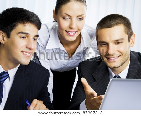 Three happy smiling successful business people working with laptop at office - stock photo