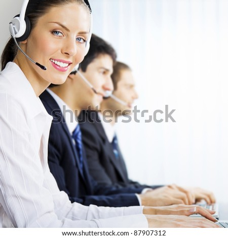 Three happy smiling young customer support phone operators at workplace - stock photo