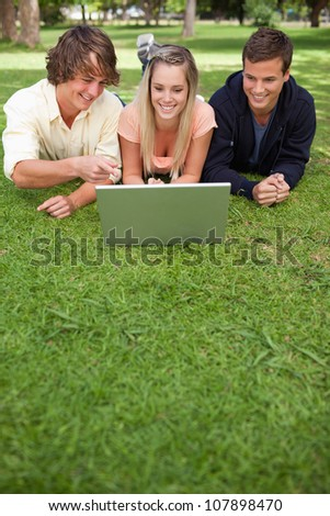 Three happy students in a park lying while using a laptop - stock photo