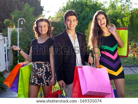 Three happy stylish teenagers out Christmas shopping standing in the street with their colourful shopping bags smiling and laughing at the camera, one young boy with two girls - stock photo