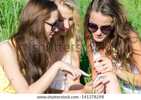 Three happy teen girl friends looking on mobile phone while sitting on green lawn on summer day - stock photo