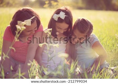 Three happy teen girls having fun at park - stock photo
