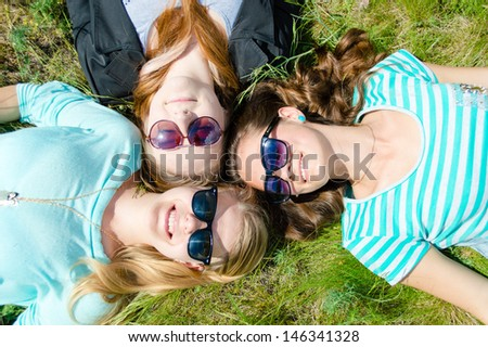 Three happy teen girls lying on green grass looking into sky in sunglasses - stock photo