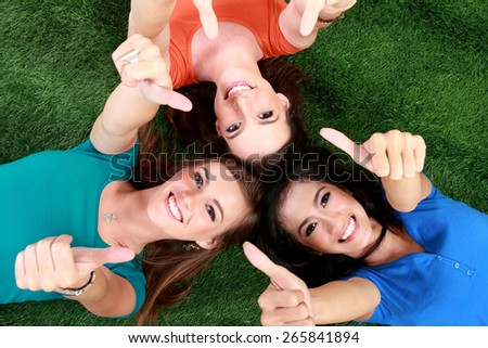 Three happy teenage girls smiling lying on the grass showing thumb up - stock photo