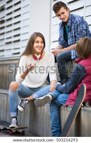 Three happy teenager friends hanging out outdoors and discussing something . Focus on girl