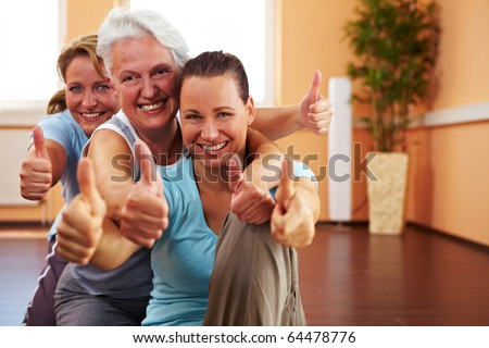 Three happy women in a gym holding their thumbs up