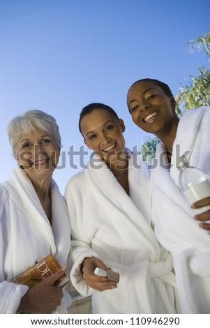 Three happy women in bathrobe - stock photo
