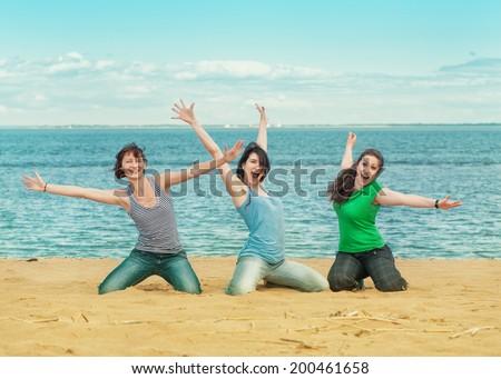 Three happy women sitting on the beach  - stock photo