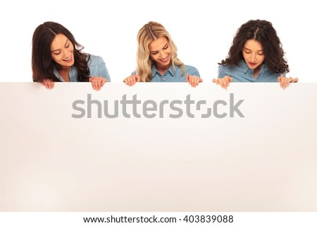 three happy young casual women looking down to a big blank board on white background - stock photo