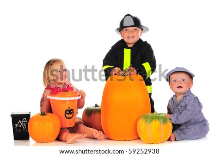 Three happy young children dressed for a happy Halloween, surrounded with pumpkins and trick-or-treat containers.  Isolated on white.