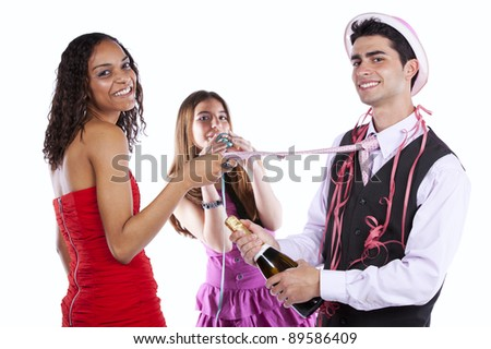 Three happy young friends celebrating the New Year party (focus on the background) - stock photo