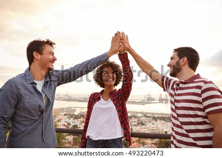 Three happy young friends doing a high five with each other while laughing and standing on a bridge that overlooks a city