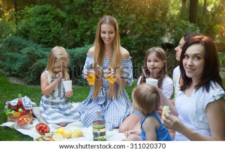 Three happy young mothers and daughters having picnic in summer park - stock photo