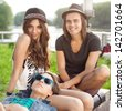 Three Happy Young People Sitting Together On Park Bench. Outdoors - stock photo