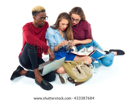 Three happy young teenager students sitting with books, laptop and bags isolated on white background