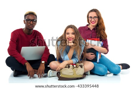 Three happy young teenager students sitting with books, laptop and bags isolated on white background - stock photo