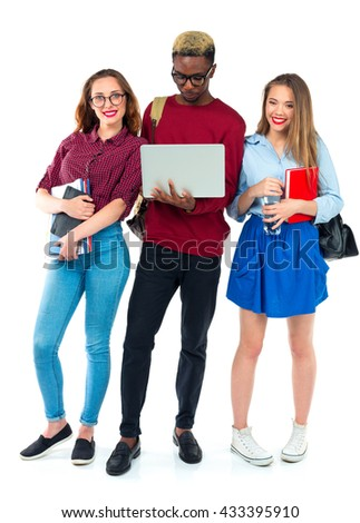 Three happy young teenager students standing and smiling with books, laptop and bags isolated on white background