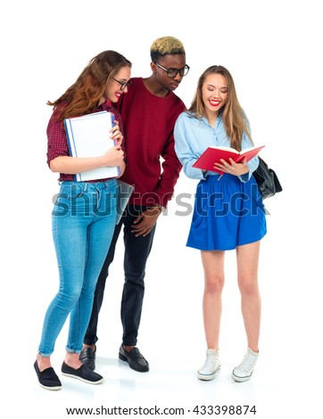 Three happy young teenager students standing and smiling with books, laptop and bags isolated on white background - stock photo