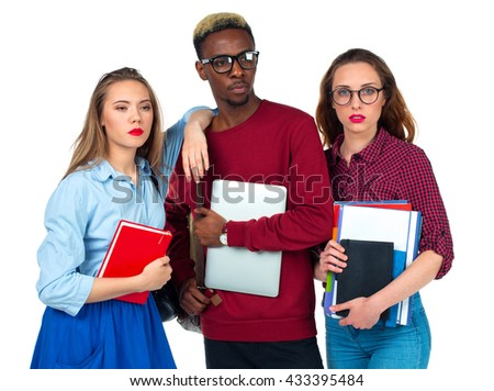 Three happy young teenager students with books, laptop and bags isolated on white background - stock photo