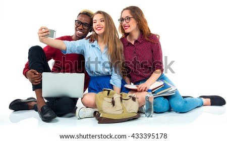 Three happy young teenager students with books, laptop, bags and makes selfie on white background - stock photo