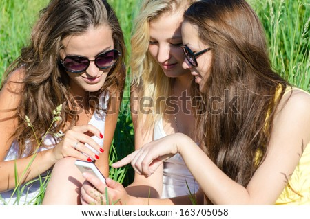 Three happy young women girl friends and mobile phone on summer outdoors background - stock photo