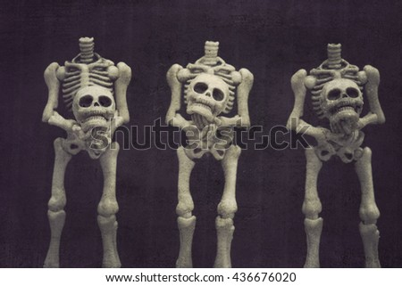 Three headless skeletons holding their heads grungy textured - stock photo