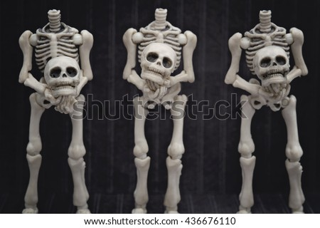 Three headless skeletons holding their heads with black background - stock photo