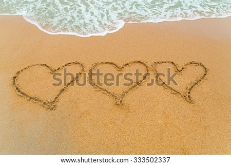 Three hearts drawn on serene sandy beach with soft blue wave approaching signifying I love You