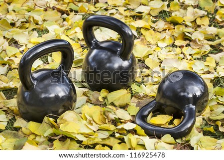 three heavy iron  kettlebells outdoors in a fall scenery  - outdoor fitness concept - stock photo