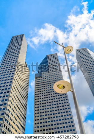 Three high-rise buildings rising up into the sky with a street light in the foreground - stock photo