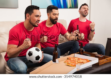 Three Hispanic male friends rooting for their soccer team on TV and celebrating a goal - stock photo