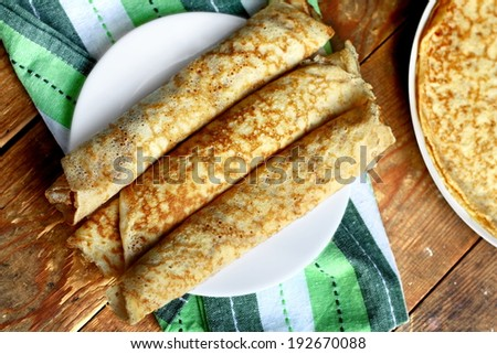 Three home made pancakes rolled on a plate