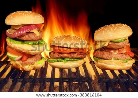 Three Homemade Cheeseburgers On The Hot BBQ Charcoal Grill With Bright Flames Of Fire On The Black Background, Close Up, Front  View, Cookout Food For Outdoor Party Or Picnic