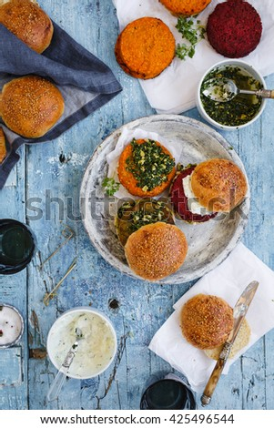 Three Homemade veggie burgers with sweet potato, chickpeas couscous, quinoa and pea sprouts, served on wooden chopping board over blue wooden table. rustic style. Top view. - stock photo