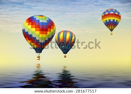 Three hot air balloons adrift over the ocean and reflecting in the water.