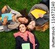 three hot college girls laying on green grass - stock photo