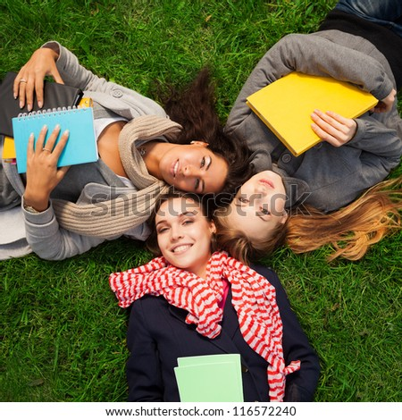 three hot college girls laying on green grass - stock photo