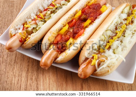 Three hot dogs on dish closeup , left with mustard , ketchup , onion and relish , middle with chili , salsa and small tomatoes, right with sauerkraut - stock photo