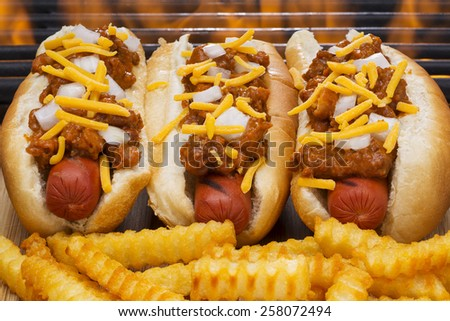 Three Hot Dogs with Mustard, Ketchup, pickle relish and onions and french fries and Flaming Barbecue Grill Background - stock photo